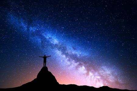 paisaje nocturno con la Vía Láctea. Silueta de un hombre de pie con los brazos levantados hacia arriba en la parte superior de la montaña. rocas altas, pico de la montaña. Hermosa Galaxy. Universo. Noche azul cielo estrellado y luces de la ciudad Foto de archivo