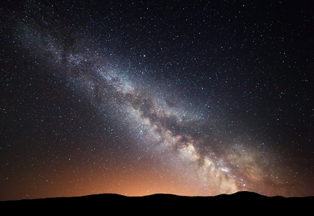 Night landscape with amazing Milky Way and yellow light at mountains. Starry sky with hills at summer. Beautiful Galaxy.l Universe. Space background 免版税图像