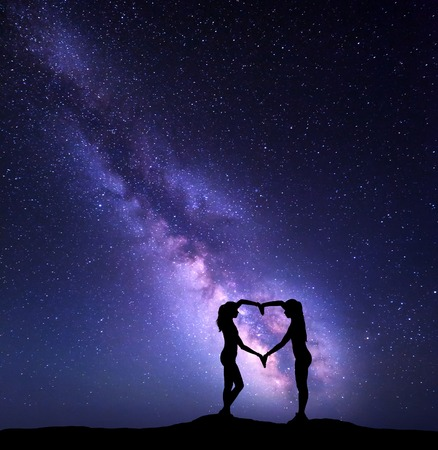 Girls holding hands in heart shape on the background of the colorful Milky Way. Night landscape with starry sky. Amazing galaxy. Silhouette of women 免版税图像
