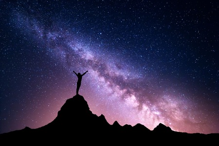 Landscape with vibrant Milky Way. Colorful night sky with stars and silhouette of a standing sporty girl with raised-up arms on the mountain peak on the background of beautiful galaxy. Banco de Imagens