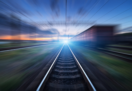 heavy effect: Railway station with cargo wagons and train light in motion at sunset. Railroad with motion blur effect. Railway platform. Heavy industry. Conceptual background Stock Photo