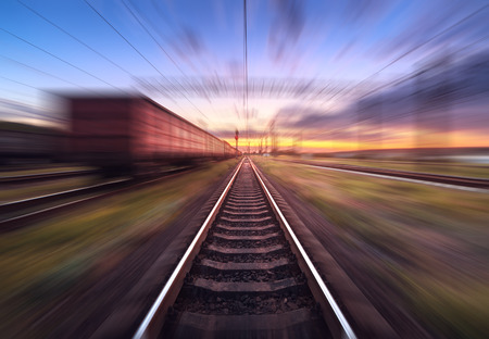heavy effect: Railway station with cargo wagons in motion at sunset. Railroad with motion blur effect. Railway platform at dusk. Heavy industry. Conceptual background