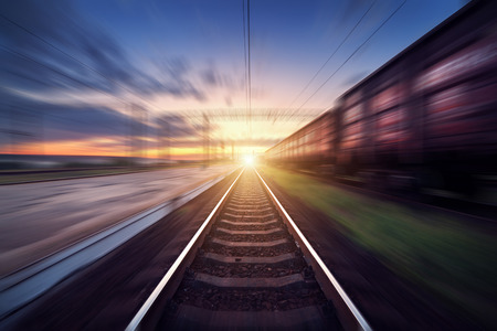 Railway station with cargo wagons and train light in motion at sunset. Railroad with motion blur effect. Railway platform. Heavy industry. Conceptual background Stock Photo