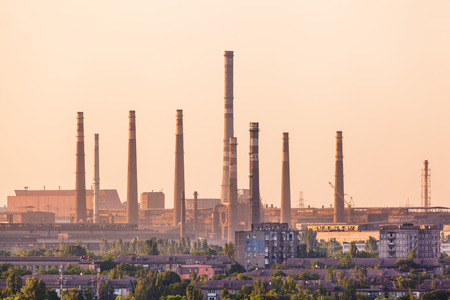 Industrial landscape. Steel factory at sunset. Pipes with smoke. Metallurgical plant. steelworks, iron works. Heavy industry in Europe. Air pollution from smokestacks, ecology problems. Vintage style
