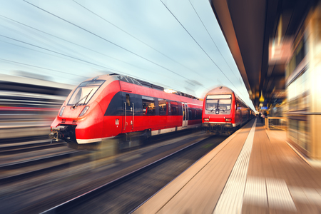 Modern high speed red passenger commuter trains at the railway platform at sunset. Railway station in Nuremberg, Germany. Railroad with motion blur effect. Industrial concept landscape. Transportation
