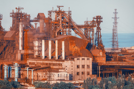 metallurgical: Industrial buildings . Steel factory at sunset. Pipes with smoke. Metallurgical plant. steelworks, iron works. Heavy industry in Europe. Air pollution from smokestacks, ecology problems. Vintage style Stock Photo