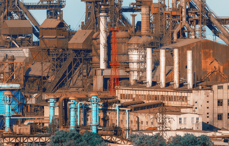 Industrial buildings . Steel factory at sunset. Pipes with smoke. Metallurgical plant. steelworks, iron works. Heavy industry in Europe. Air pollution from smokestacks, ecology problems. Vintage style Stock Photo