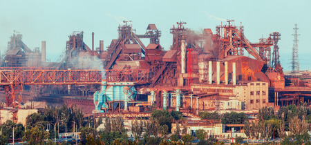 Metallurgical plant. Industrial landscape. Steel factory at sunset. Pipes with smoke. steelworks, iron works. Heavy industry in. Air pollution from smokestacks, ecology problems. Vintage style Stock Photo