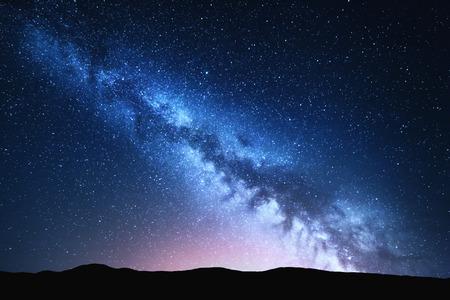 Milky Way en roze licht bij bergen. Night kleurrijk landschap. Sterrenhemel met heuvels in de zomer. Mooie Universe. Ruimte achtergrond met melkweg. reizen achtergrond Stockfoto