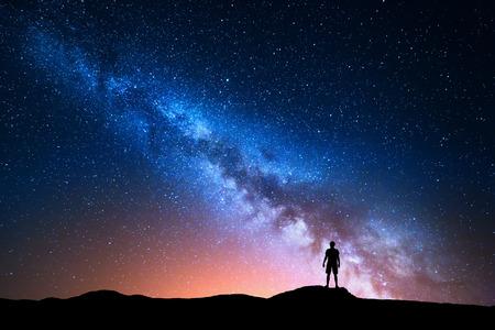 Melkweg. Mooie nachthemel met sterren en silhouet van een staande alleenstaande man op de berg. Blauwe melkachtige manier met rood licht en man op de heuvel. Achtergrond met melkweg en silhouet van een man. Universum