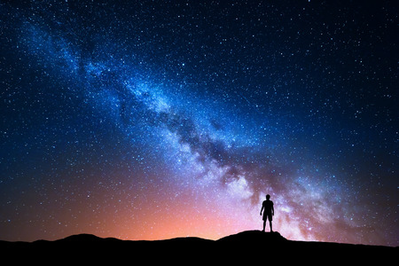 Milky Way. Beautiful night sky with stars and silhouette of a standing alone man on the mountain. Blue milky way with red light and man on the hill. Background with galaxy and silhouette of a man. Universe Stock fotó - 65611040