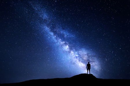 Milky Way. Beautiful night sky with stars and silhouette of a standing alone man on the mountain. Blue milky way with man on the hill. Background with galaxy and silhouette of a man. Universe