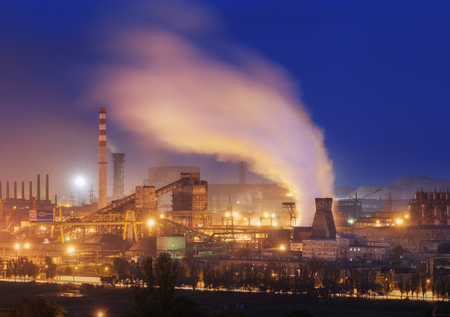 Metallurgical plant at night. Steel factory with smokestacks. Steelworks, iron works. Heavy industry in Europe. Air pollution from smokestacks, ecology problems. Industrial landscape at dusk. Plant