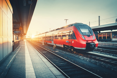Beautiful railway station with modern high speed red commuter train at colorful sunset. Railroad with vintage toning. Train at railway platform. Industrial concept. Railway tourism Standard-Bild