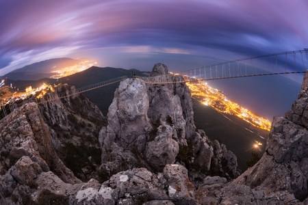 Mountain landscape with beautiful clouds and city lights at night. Beautiful colorful night landscape with mountain peak with bridge. High rocks against blue sky with purple clouds. Nature background