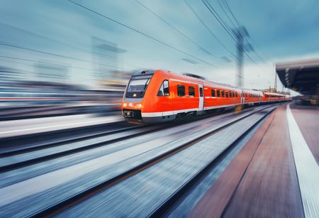 Modern high speed red passenger commuter train in motion at the railway platform. Railway station. Railroad with motion blur effect. 新闻类图片