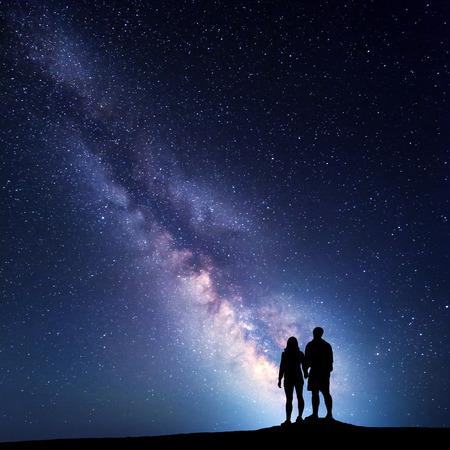 Milchstraße mit Menschen auf dem Berg. Landschaft mit Nachthimmel mit Sternen und Silhouette von stehenden Mann und Frau. Milchstraße mit Paar Reisende gegen schöne Galaxie. Universum