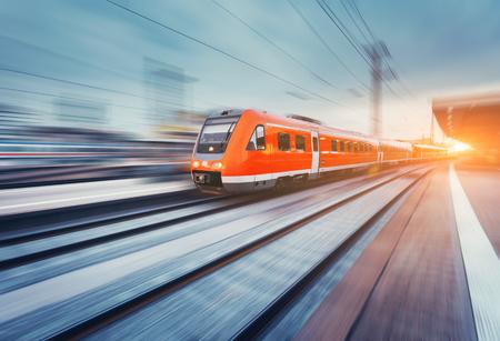 현대 고속 빨간색 승객 통근 기차 석양 철도 플랫폼에서 모션. 기차역. 철도 모션 흐림 효과. 기차로 산업 프리입니다. 빈티지 토닝