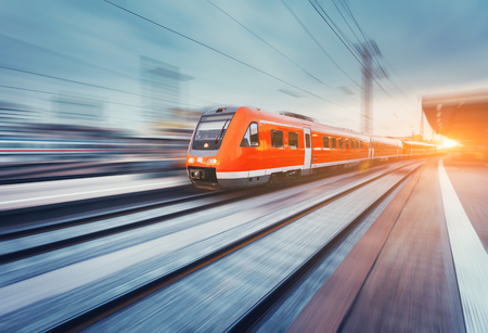 Modern high speed red passenger commuter train in motion at the railway platform at sunset. Railway station. Railroad with motion blur effect. Industrial landscape with train. Vintage toning 免版税图像