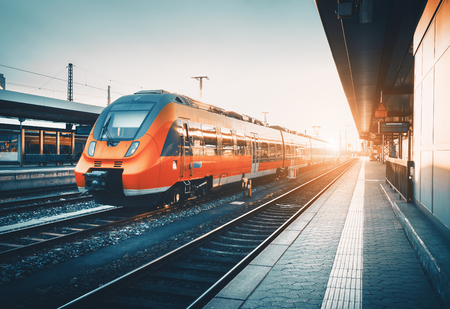 Modern high speed red commuter train at the railway station at colorful sunset. Railroad with vintage toning. Train at railway platform. Industrial landscape. Railway tourism. Vintage toning. Concept