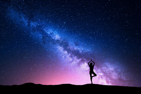 Milky Way with silhouette of a standing woman practicing yoga on the mountain. Beautiful landscape with meditating girl against night starry sky with milky way. Amazing galaxy. Universe. Travel  免版税图像