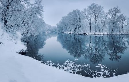 Winter bos aan de rivier bij zonsondergang. Kleurrijk landschap met besneeuwde bomen, mooie bevroren rivier met reflectie in het water. Seizoensgebonden. bomen winter, meer en blauwe hemel. Ijzige besneeuwde rivier. Weer