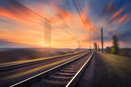 Railroad en mouvement au coucher du soleil. Gare avec effet de flou de mouvement contre le ciel bleu coloré, concept fond industriel. Voyage de chemin de fer, le tourisme ferroviaire. ferroviaire flou. Transport