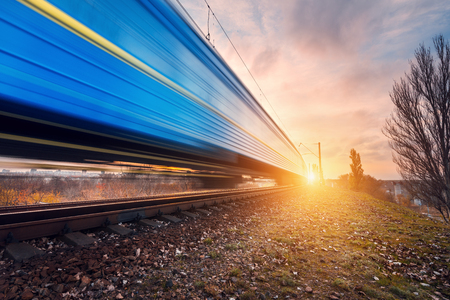 High speed blue passenger train on railroad track in motion at sunset. Blurred commuter train. Railway station. Railroad travel, railway tourism. Industrial landscape in the evening in autumn. Concept