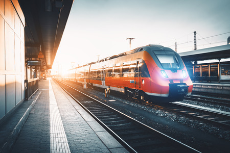 Treno pendolare rosso ad alta velocità moderno alla stazione ferroviaria al tramonto. Accensione dei fari del treno. Ferrovia con viraggio vintage. Treno alla piattaforma ferroviaria. Paesaggio industriale Turismo ferroviario