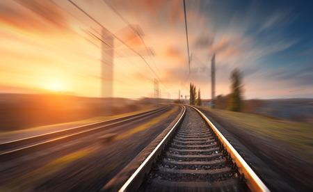 Spoorweg in motie bij zonsondergang. Treinstation met motion blur effect tegen kleurrijke blauwe hemel, Industriële concept achtergrond. Railroad reizen, spoorweg toerisme. Wazig spoorweg. vervoer
