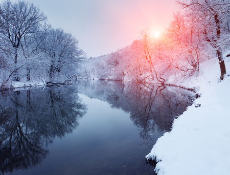 Winter forest on the river at sunset. Colorful landscape with snowy trees, beautiful frozen river with reflection in water, sun. Seasonal. Winter trees, lake and blue sky. Frosty snowy river. Weather Stock Photo