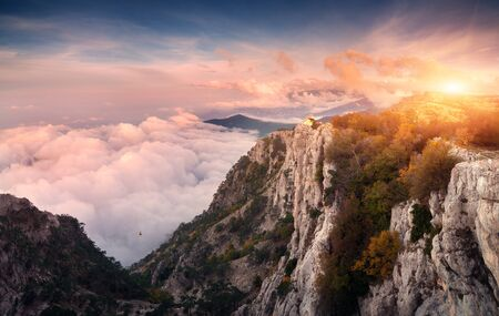Panoramic mountain landscape at sunset. Amazing view from mountain peak on the high rocks, sky, clouds and trees in the evening. Low clouds. Colorful nature background. Adventure. Travel in Crimea