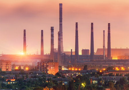 metallurgical: City buildings on the background of steel factory with smokestacks at sunset. Metallurgical plant with chimney. steelworks, iron works. Heavy industry. Air pollution, smog. Industrial landscape Stock Photo