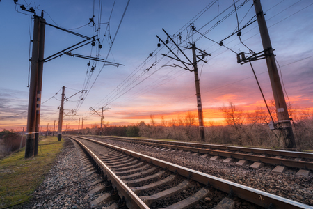 Railway station against beautiful sky at sunset. Industrial landscape with railroad, colorful blue sky with red clouds. Railway junction. Heavy industry. Cargo shipping. Railway sleepers. Travel