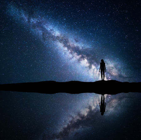 Milky Way. Night starry sky and silhouette of a standing woman on the mountain near the lake with sky reflection in water. Landscape with blue Milky Way and woman. Galaxy, Universe. Space background.