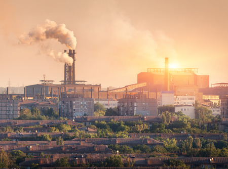 metallurgical: Metallurgy plant at sunset. Steel mill. Heavy industry factory. Steel factory with smog. Pipes with smoke. Metallurgical plant in city. steel, iron works. Ecology problems, atmospheric pollutants Stock Photo