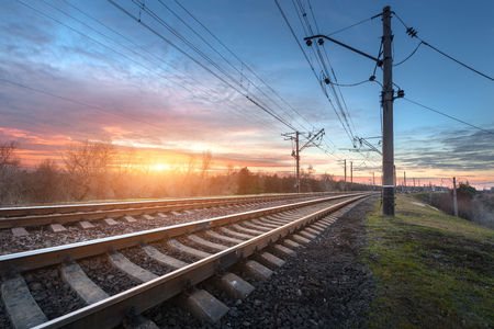 Railway station against beautiful sunny sky. Industrial landscape with railroad, blue sky and colorful clouds at sunset . Railway junction in the evening. Heavy industry. Cargo shipping. Travel