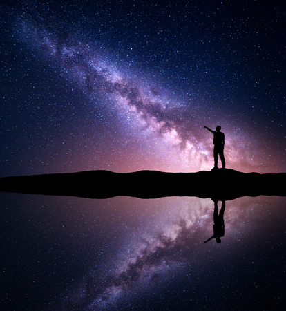 Milky Way. Silhouette of a standing man pointing finger in night starry sky on the mountain near the river with sky reflection in water. Night landscape with galaxy. Purple milky way and man. Universe 免版税图像