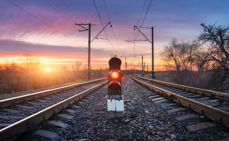 Railway station with semaphore against sunny sky with clouds at sunset. Colorful industrial landscape. Railroad. Railway platform with traffic light in the evening. Heavy industry. Cargo shipping Stock Photo
