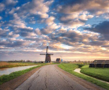 molino de agua: Camino con el molino de viento en la salida del sol en los Países Bajos. Hermoso viejo molino de viento holandés contra el cielo con nubes de colores. paisaje de primavera por la mañana en Holanda. Camino rural. Antecedentes de viaje. Naturaleza. Europa