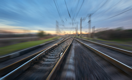 Railroad in motion at sunset. Railway station with motion blur effect against blue sky, Industrial concept background. Railroad travel, railway tourism. Blurred railway in dusk. Transportation