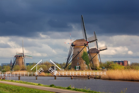 Windmills against cloudy sky at sunset in famous Kinderdijk, Netherlands. Rustic landscape with traditional dutch windmills, bridge, water and blue sky in sunrise. Sights in Holland. Travel in Europe