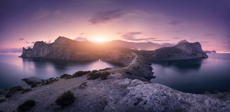 夕暮れ時のカラフルな曇り空を背景の美しい山々。夏の岩、海、山の道、森林、紫の空と街の明かりのある風景します。自然と旅行。ぼやけた雲。 写真素材