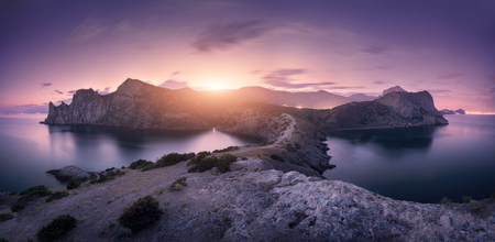 Beautiful mountains against colorful cloudy sky at sunset. Landscape with rocks, sea, mountain trail, forest, purple sky and city lights in summer. Nature and travel. Blurred clouds. Panoramic view