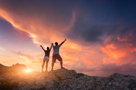 山の夕暮れ時のカラフルな空で幸せな人々 のシルエット。立っている人と山の頂上に上がっている腕を持つ女性のシルエットの夏の風景します。カ
