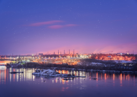 Night cityscape with colorful purple sky with stars, rocks, river, trees, buildings, city illumination and steel factory with smokestack in winter. Industrial landscape in Ukraine at twilight