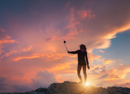 Beautiful young woman makes selfie for Instagram at sunset. Landscape with girl is photographing herself on the mountain peak against colorful sky with orange and red clouds. Lifestyle background   Stock Photo
