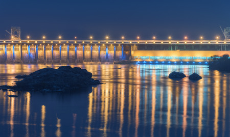 hydroelectric station: Dam at night. Beautiful industrial landscape with dam hydroelectric power station, bridge, river, city illumination reflected in water, rocks and sky. Dniper River, Zaporizhia, Ukraine.