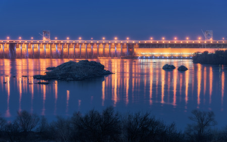 Dam at night. Beautiful industrial landscape with dam hydroelectric power station, bridge, river, city illumination reflected in water, rocks and sky. Dniper River, Zaporizhia, Ukraine.