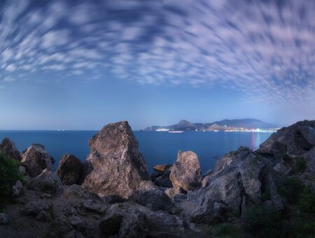 Majestic high rocks and stones glowing by moonlight at the sea. Fantastic night panoramic landscape with mountains, city lights, starry sky with clouds and blue sea in summer. Amazing scene. Nature